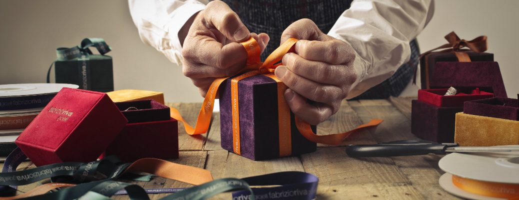 Hands tying a bow on a present