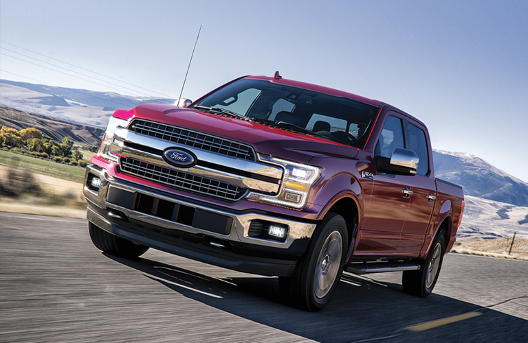 A red 2020 Ford F-150 driving down an open road.