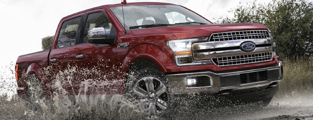 A dark red 2020 Ford F-150 driving through a puddle of mud.