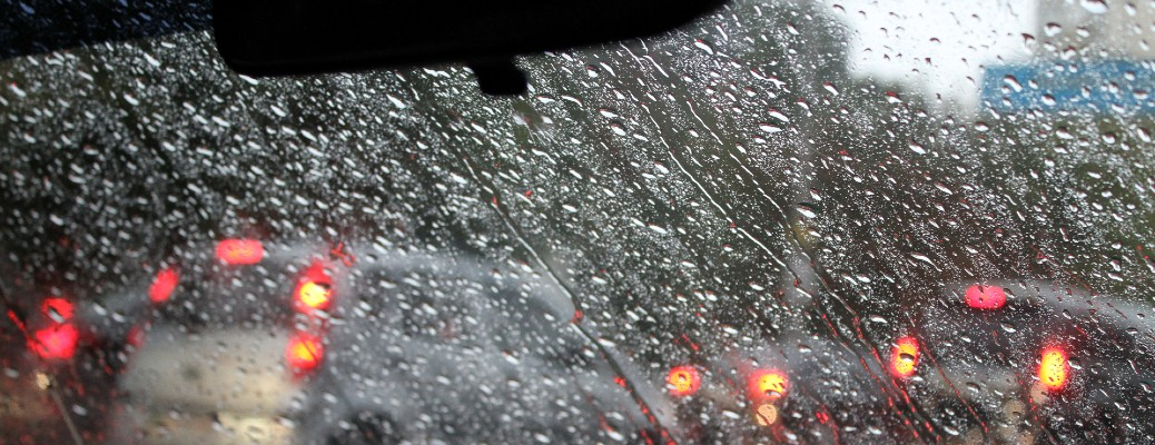 An image of water droplets on a windshield in traffic.