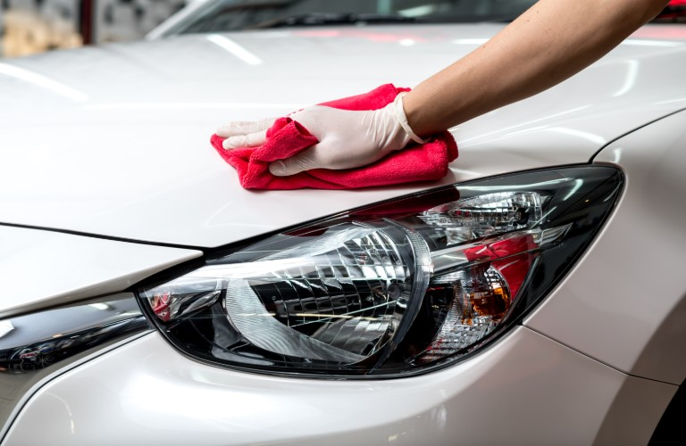 A person wiping off a white car with a red cloth.