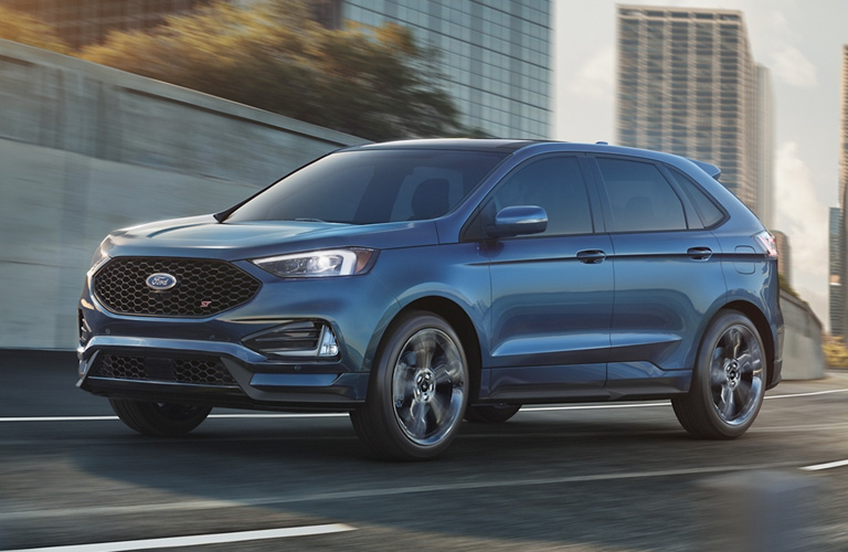 A blue 2020 Ford Edge driving down a town road.