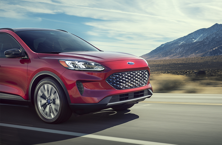The front side of a red 2020 Ford Escape Hybrid driving down a road.