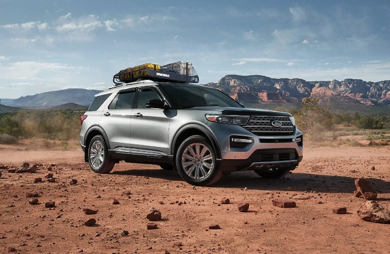 The front and side view of a gray 2021 Ford Explorer driving on a smooth off-road area.