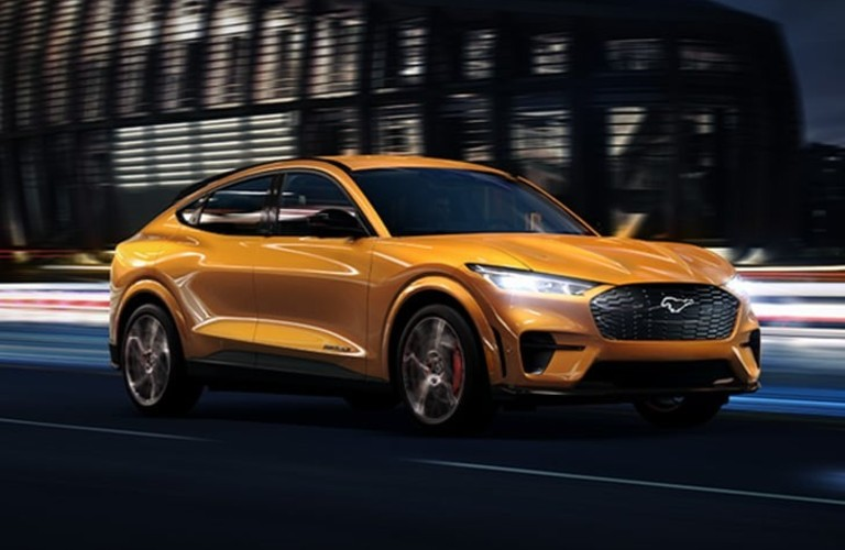 The front and side view of a yellow 2021 Ford Mustang Mach-E driving at night.