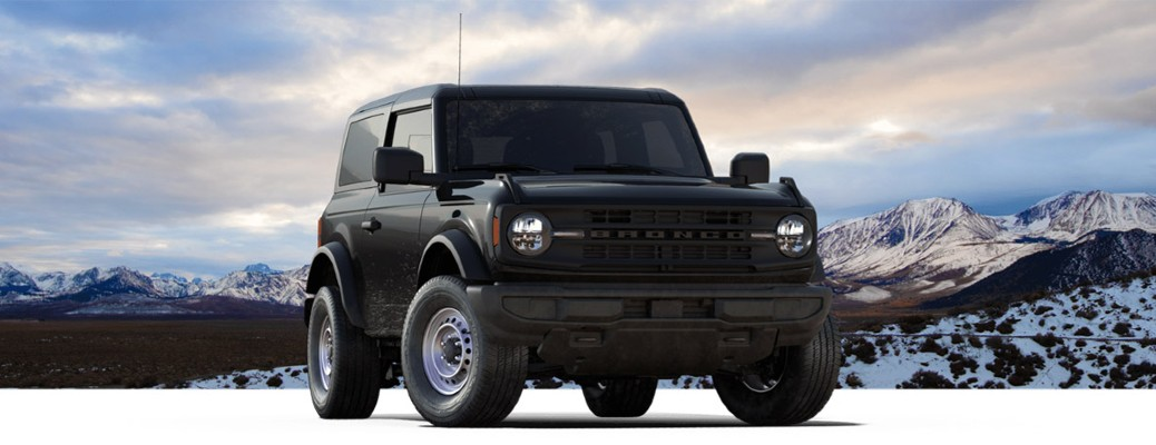 The front side of a dark green 2021 Ford Bronco Base parked in front of mountains.