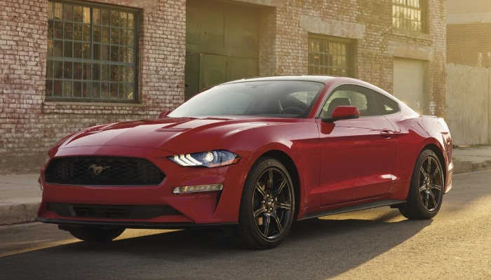 2021 Ford Mustang parked in front of a brick building at sunset.