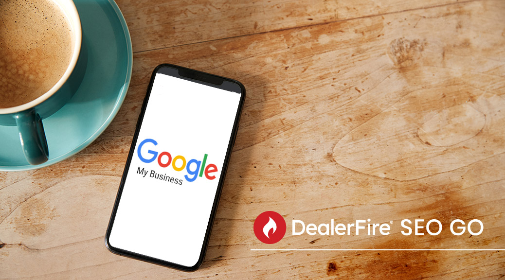 Google My Business logo shown on smartphone on table beside coffee with DealerFire SEO Go text