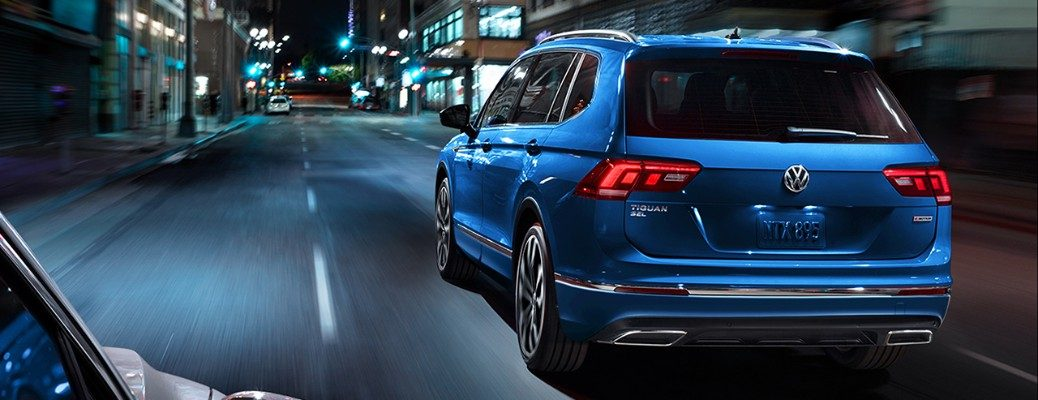 Rear view of blue 2020 Volkswagen Tiguan driving on dark city road