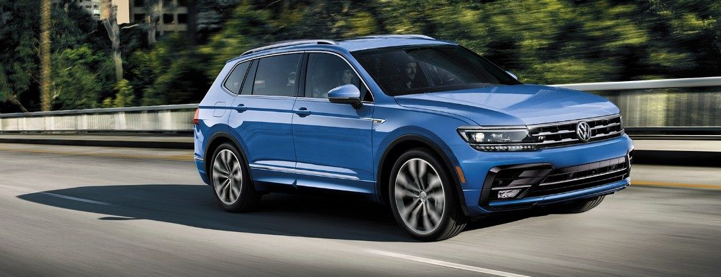 People driving inside blue 2020 VW Tiguan