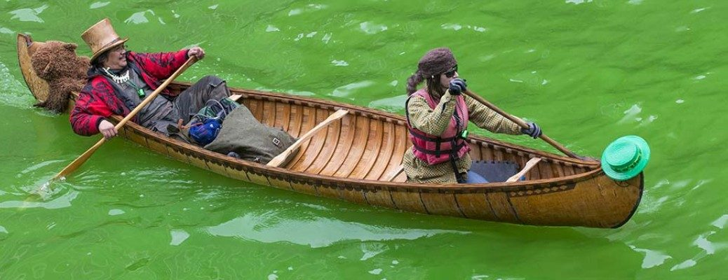 Two people rowing in a boat down a green river for St. Patrick's Day
