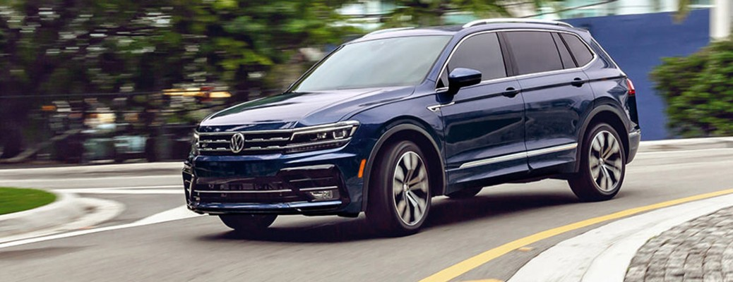 2021 Volkswagen Tiguan driving down a curved road with trees in the background