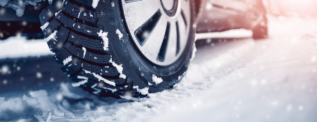 A close up photo of a car tire driving through snow
