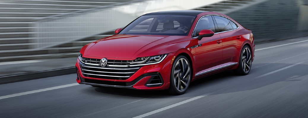 A red-colored 2021 Volkswagen Arteon driving on a road