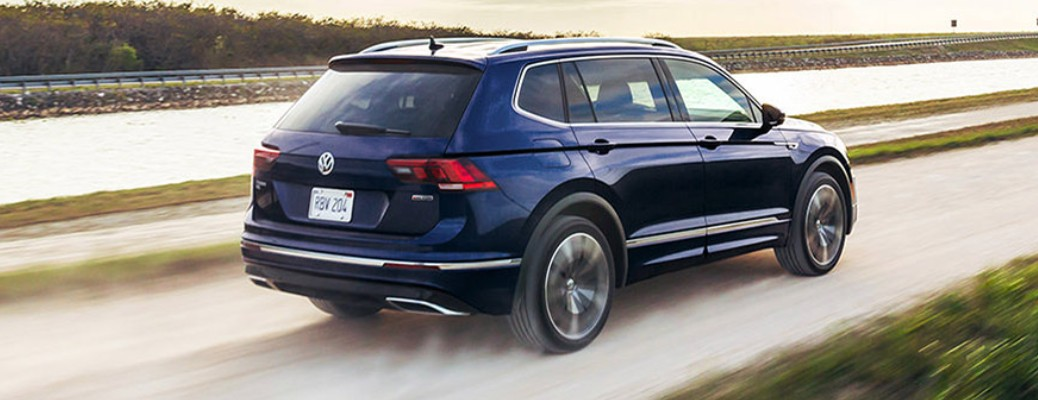 A blue-colored 2021 Volkswagen Tiguan driving on the road