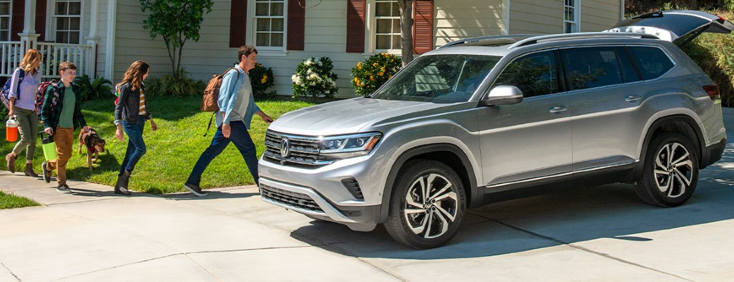 Four members of a family walk away from their home and toward a 2021 Volkswagen Atlas, which is parked in their driveway