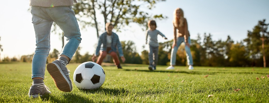 Four kids playing outside in the grass with a soccer ball