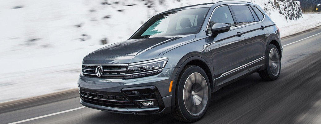 A 2021 Volkswagen Tiguan driving on a road near snow