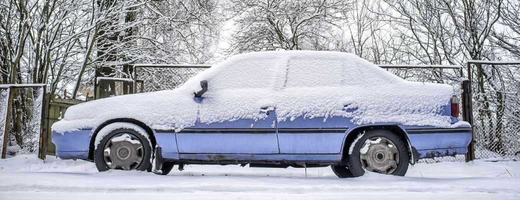 A parked blue car covered in snow