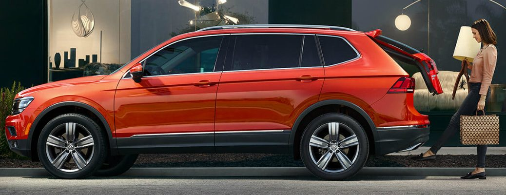 Woman operating power liftgate of orange 2019 Volkswagen Tiguan