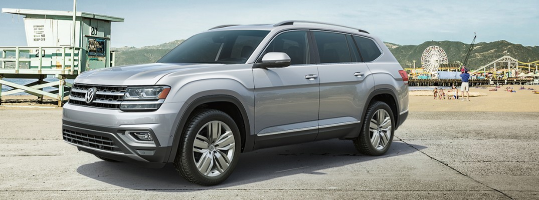 Silver VW Atlas parked with pier in background