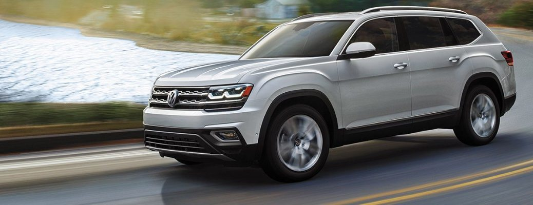Silver 2019 VW Atlas driving on waterfront curved road