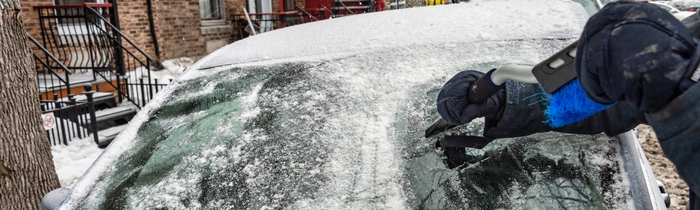 Man using ice scraper to clear car windshield