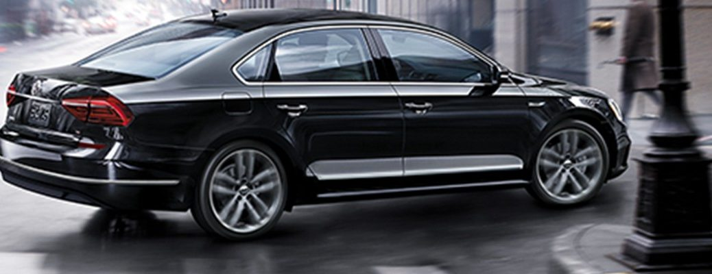 Black 2019 Volkswagen Passat driving around city street corner