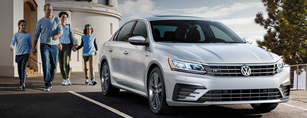 Large family walking towards silver 2019 Volkswagen Passat