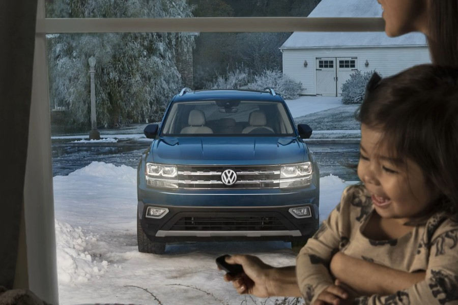 Front view of a blue 2019 Volkswagen Atlas parked outside in winter and a woman holding a child using remote start inside