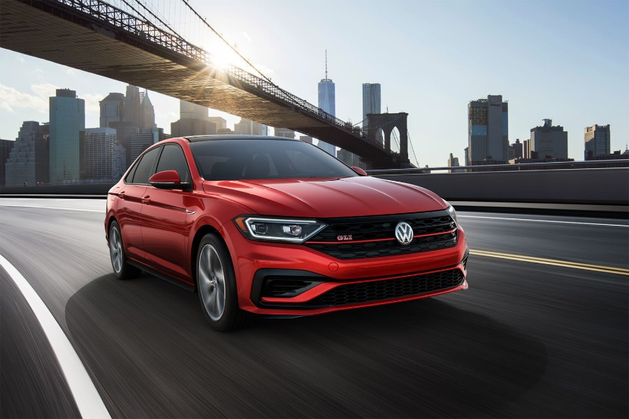 Front passenger angle of a red 2019 Volkswagen Jetta GLI driving down a road with a city in the background