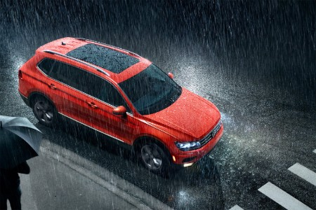Front passenger aerial angle of an orange 2019 Volkswagen Tiguan driving through rain