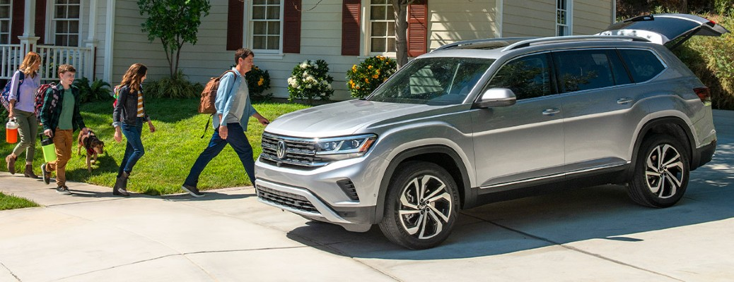 A family of four walking toward a 2021 Volkswagen Atlas parked in a driveway near a house