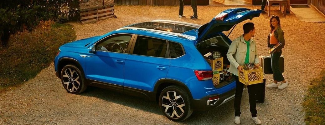 A man unloading a basket from the 2022 Volkswagen Taos.