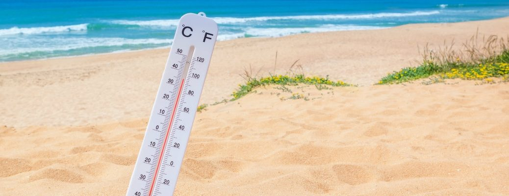 Thermometer stuck in the sand at the beach