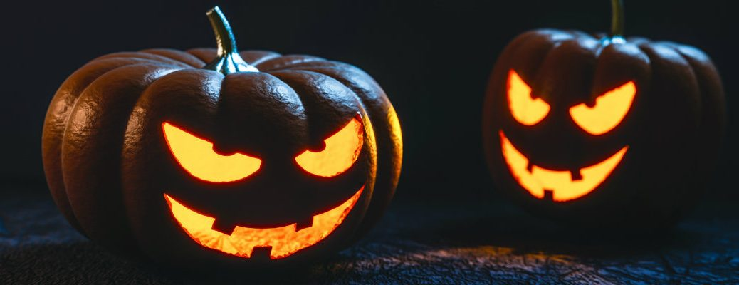 Pair of carved pumpkins that are lit up