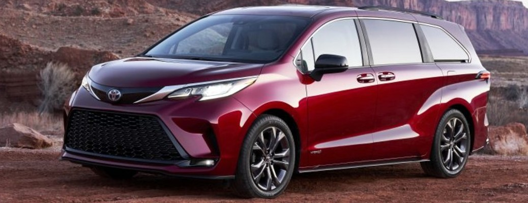 Red Toyota Sienna in front of rustic canyon backdrop