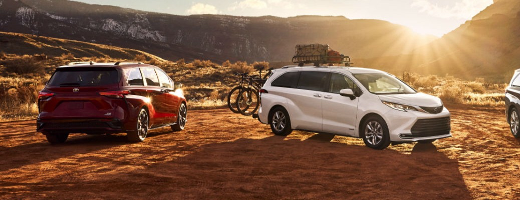 Two 2021 Toyota Sienna's parked by each other in front of mountain terrain