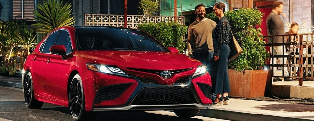 Two individuals standing outside of a red Toyota Camry