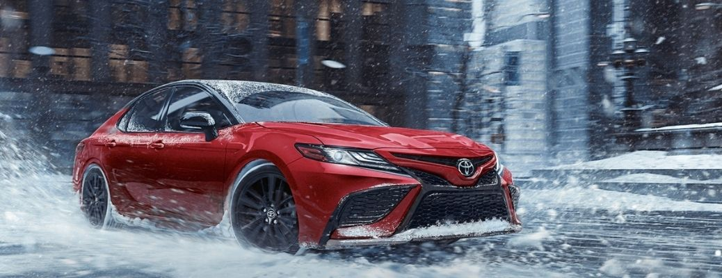 2021 Toyota Camry Hybrid in red color quarter view splashing snow