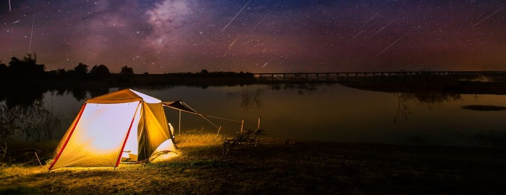a camping tent set up by the lake at night in an open field