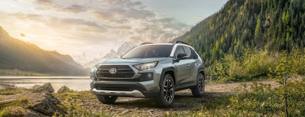 front and side view of the 2021 Toyota RAV4 parked near mountains and greenery