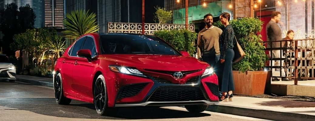 View of the 2022 Toyota Camry Hybrid in red near a building with people standing near it