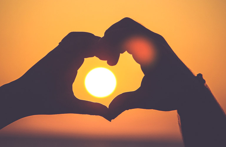Two hands forming a heart in front of the sun
