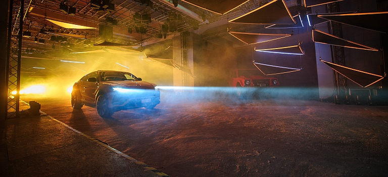 Lamborghini Urus front view driving through fog on a stage