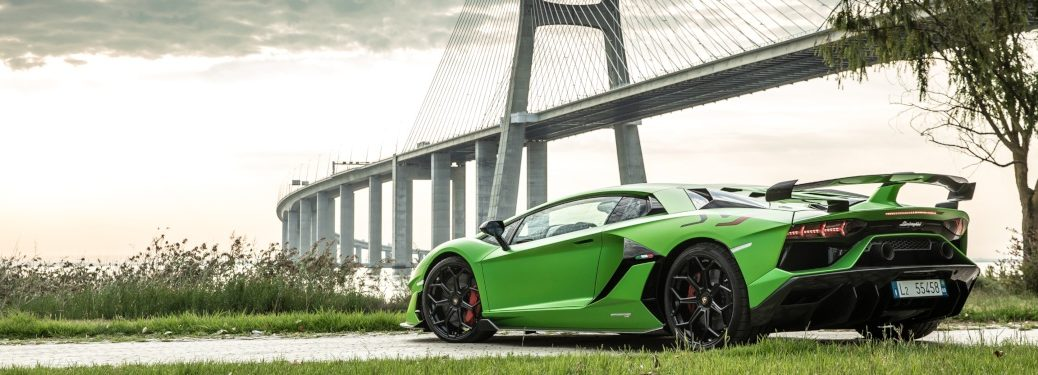 Lamborghini Aventador SVJ green side back view in front of a bridge