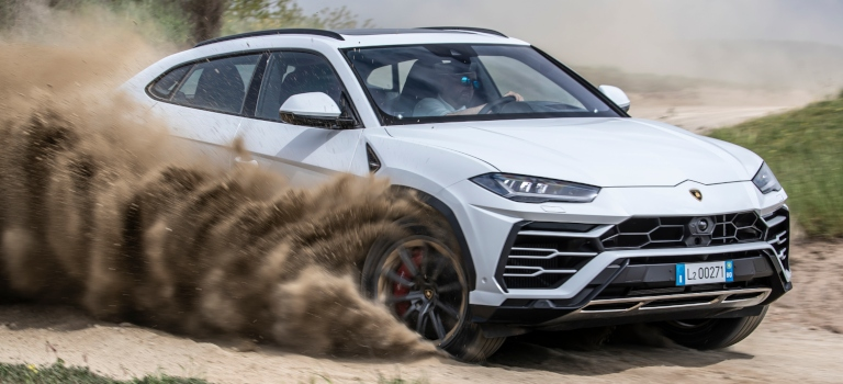 Lamborghini Urus white side view spraying up dirt