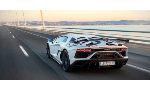 2020 Lamborghini Aventador SVJ white paint driving away from shot across long suspension bridge