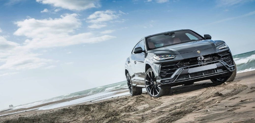 2020 Lamborghini Urus grey tilted shot on beach with waves in background
