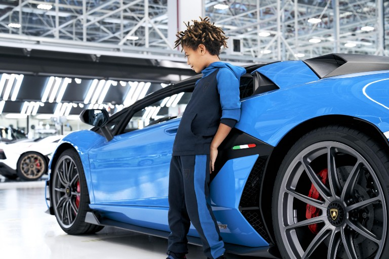 Kid in blue Lamborghini clothes leaning on a blue Lamborghini
